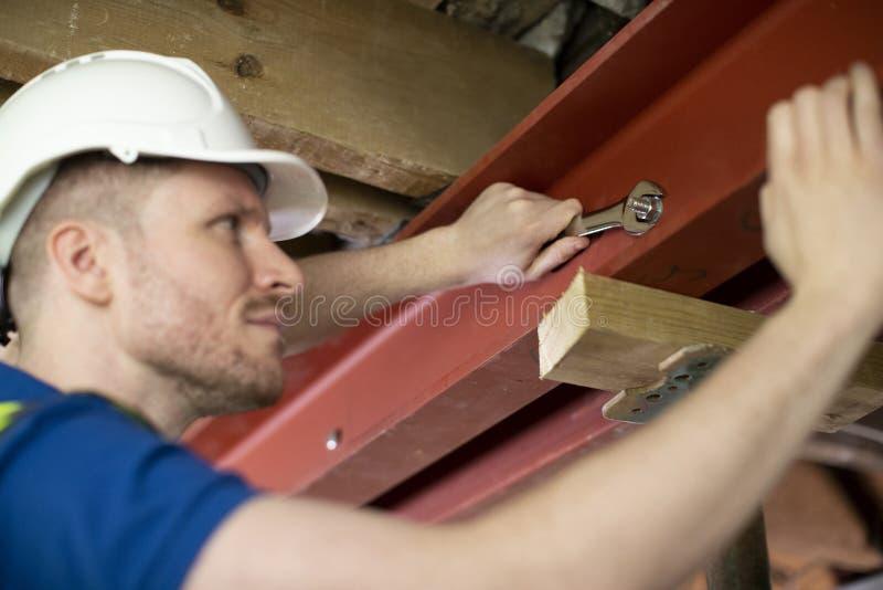 Haz de ayuda de acero del trabajador de construcción que cabe en techo renovado de la casa imagenes de archivo