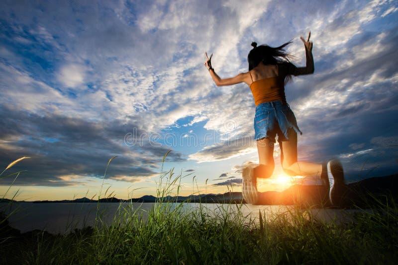Haz de la nube de la puesta del sol al woma asiático adulto joven imagenes de archivo