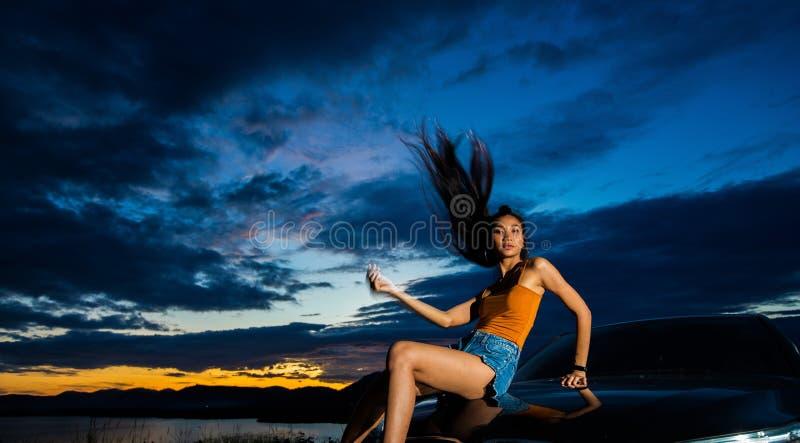 Haz de la nube de la puesta del sol al woma asiático adulto joven imagen de archivo libre de regalías