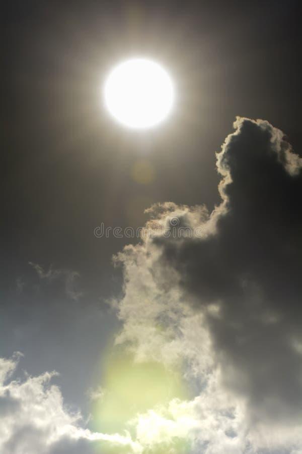 Haz de Sun en nubes y cielo oscuros imagen de archivo