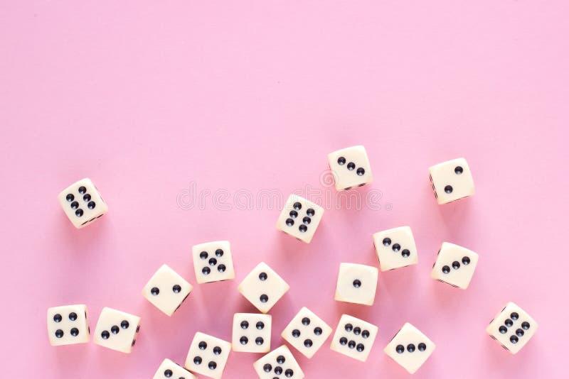 Hazardów kostka do gry z kopii przestrzenią na różowym tle obraz stock