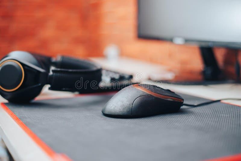 Hazard areny tło z myszy przekładni hełmofonów komputerem, focuse na myszy wybierał focuse zdjęcia royalty free