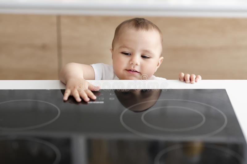 Curious toddler reaching hand to hot electric cooktop royalty free stock photos