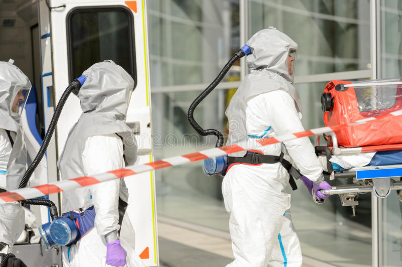 Hazardous material medical team entering building. Hazardous material medical team with stretcher entering contaminated building royalty free stock images