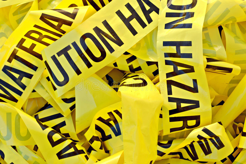 Hazardous Material Tape. Pile of yellow plastic tape marked Cautious Hazardous Material stock photos