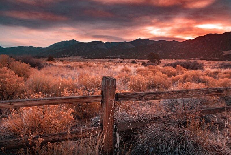 Haze Sunset Overlooking arancio un prato immagine stock libera da diritti