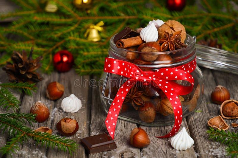 Hazelnoten en okkernoten met snoepjes en kruiden in een glaskruik royalty-vrije stock foto