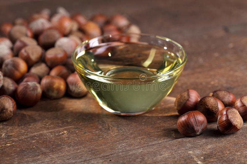 Hazelnut Oil. Small glass bowl with hazelnut oil and a few whole hazelnuts royalty free stock image