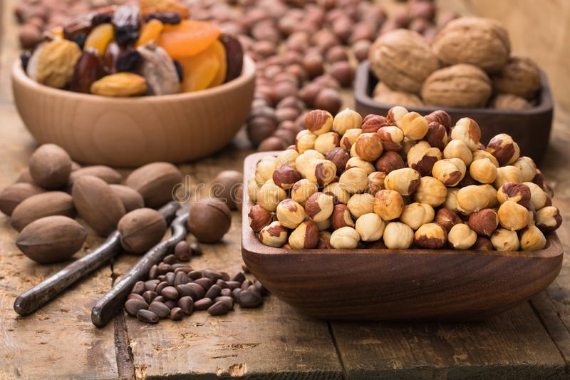 Hazelnut peeled roasted in wooden bowl on table, grunge style stock photo