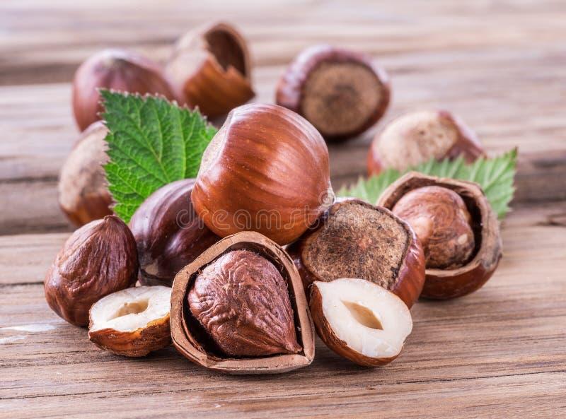 Hazelnuts i hazelnut opuszczają na drewnianym stole zdjęcie royalty free