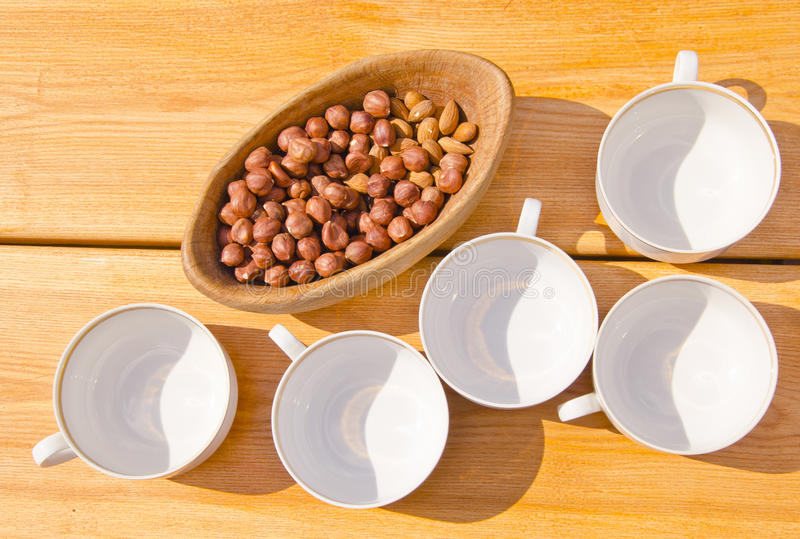 Hazelnuts pack in wooden dish cups placed on table. Hazelnuts packed in wooden dish and cups placed on table outside illuminate sun and shadows stock images
