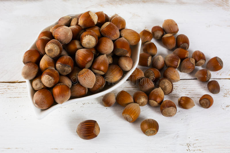 Hazelnuts on white wooden background royalty free stock photo