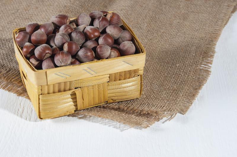Hazelnuts in a wicker basket on burlap on white wooden background. Healthy food for people involved in sports and health conscious royalty free stock photos