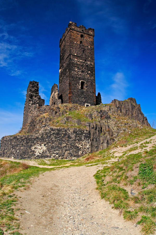 Hazmburk gothic castle on rocky mountain, with gravel path and blue sky, in Ceske Stredohori, Czech republic. stock images