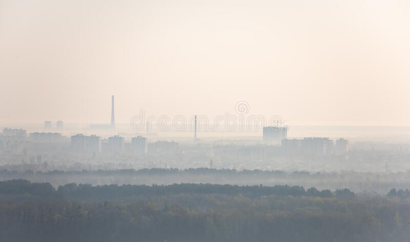 Hazy morning view on left riverside of Dnieper river in Kyiv, Ukraine. Silhouettes of residential houses and factory pipes, skyline, haze, mist, fog, foggy stock images