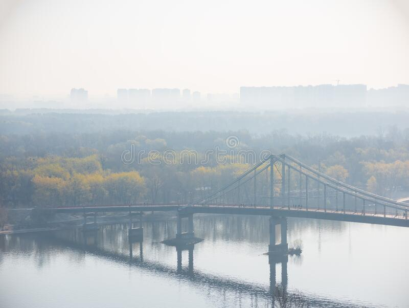 Hazy morning view on pedestrian Park Bridge, Trukhaniv island and left riverside of Dnieper river in Kyiv, Ukraine. Skyline, haze, mist, fog, foggy, arch royalty free stock photos