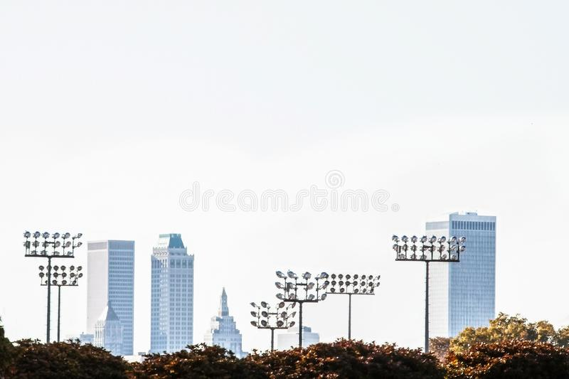 Hazy view of Tulsa skyline from University of Tulsa campus with a high floodlight in the foreground - soft focus with blur in zdjęcia royalty free