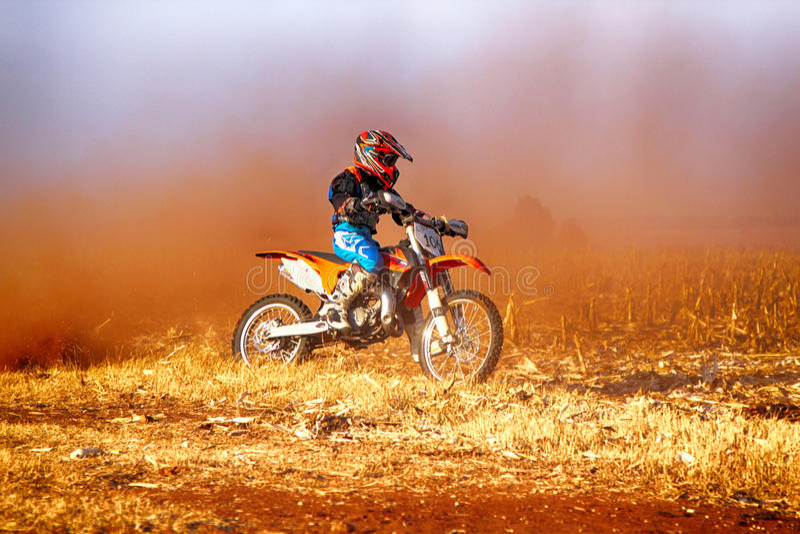 HD -踢尘土的足迹在沙子轨道dur的小辈摩托车 库存图片