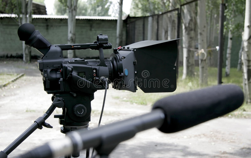 Hd camcorder. Stand high definition camcorder on nature shooting and studio microphone in bluring front stock image