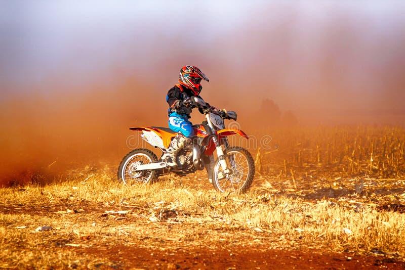 HD - Junior Motorbike som upp sparkar slingan av damm på sandspårdur fotografering för bildbyråer