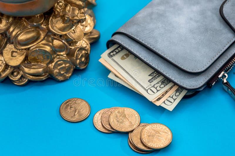 Hdollar plånbokintelligens och oss mynt på blått royaltyfria bilder
