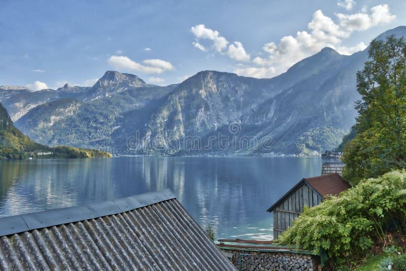 HDR山风景视图与剧烈的多云天空的在Hallstatt村庄附近的一个湖上在奥地利 免版税库存照片