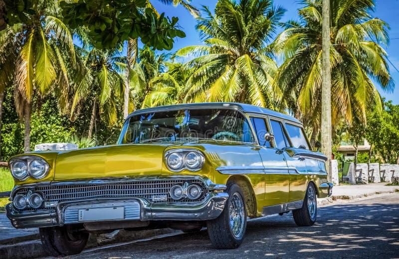 HDR - Американский золотой Форд Brookwood припаркованное под ладонями около пляжа в Варадеро Кубе - репортаже Serie Кубы стоковое фото