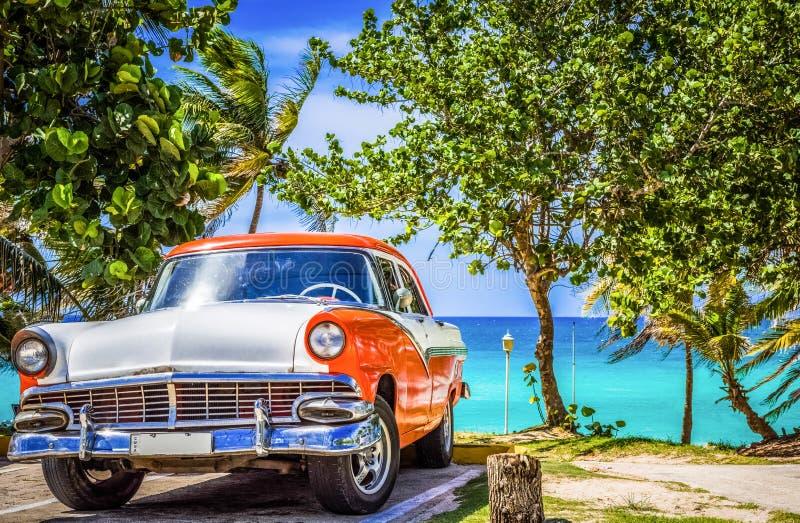 HDR -在正面图的停放的美国白色橙色福特Fairlane葡萄酒汽车在巴拉德罗角古巴- Serie古巴Reportag的海滩 图库摄影