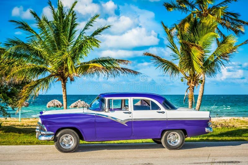 HDR - Amerikanisches weißes blaues Weinleseparkauto in der VorderSideansicht über den Strand in Havana Cuba - Reportage Serie Kub stockfotografie