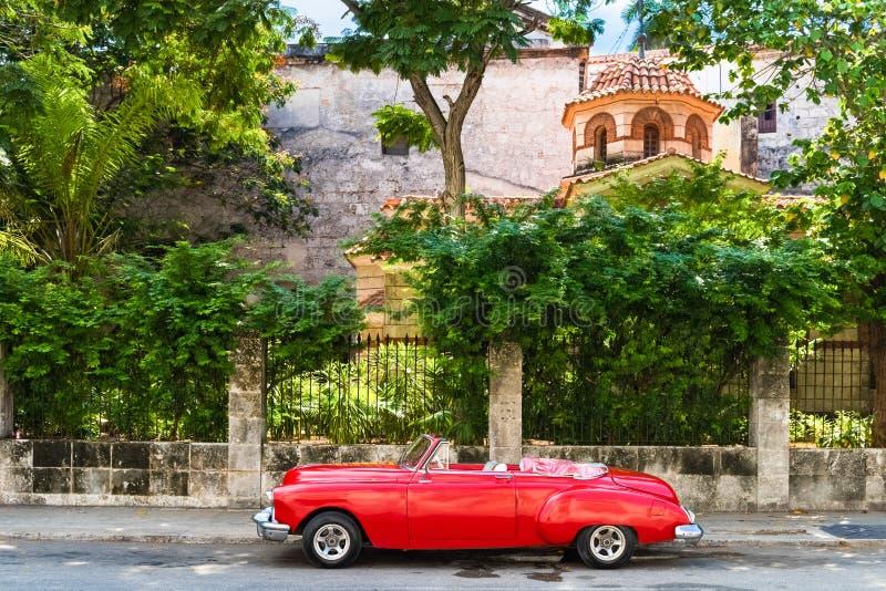 HDR - Amerikansk röd Oldsmobile konvertibel tappningbil som parkeras på Maleconen för en fästning el Morro i Havana Cuba - den Se arkivfoton