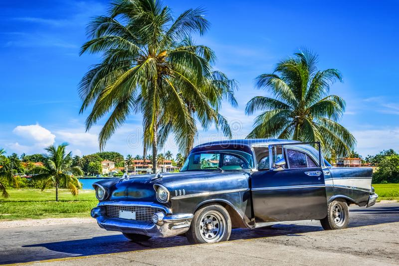 HDR - Amerykański czarny rocznika samochód parkujący pod palmami blisko plaży w Varadero Kuba, Seria Kuba reportażu - zdjęcie royalty free