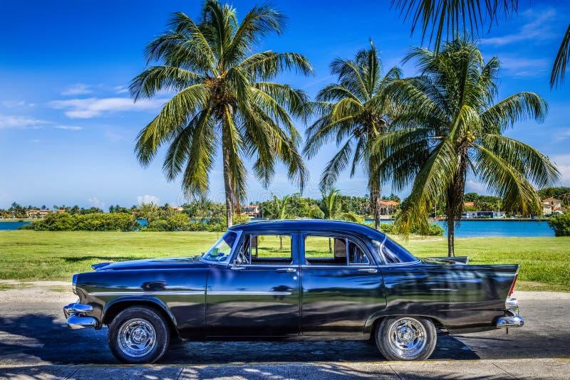 HDR - Amerykański czarny rocznika samochód parkujący pod palmami blisko plaży w Varadero Kuba, Seria Kuba reportażu - fotografia stock