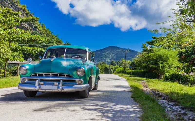 HDR - Błękitnej zieleni rocznika amerykański samochód jedzie na countrystreet w wsi od Trinidad Kuba, Seria Kuba reportażu - zdjęcie stock