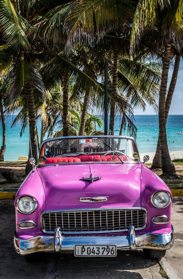 HDR Cuba pink american Oldtimer parked under palms near the beach in Varadero.  royalty free stock photos