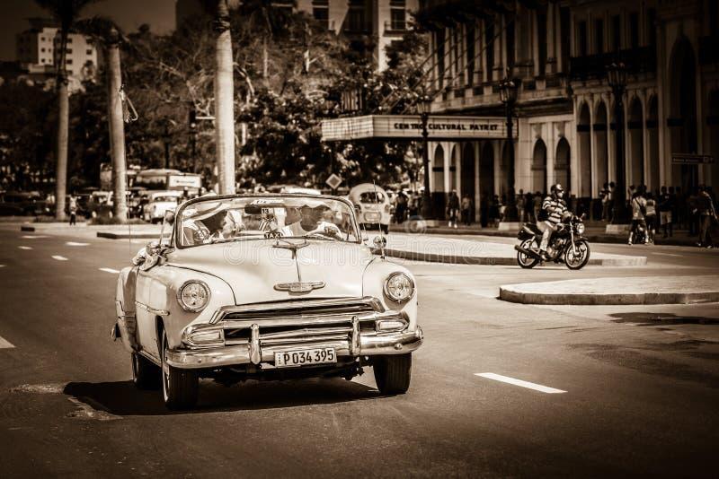 HDR - Den amerikanska Cabriolettappningbilen kör med turister på den huvudsakliga gatan i Havana Cuba - R arkivbilder