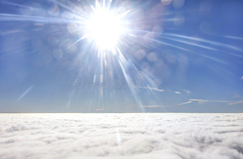 HDR foto av en flygplanvinge mot den blåa himlen med en molnräkning under och den glänsande solen för brigh in framme av den royaltyfri bild