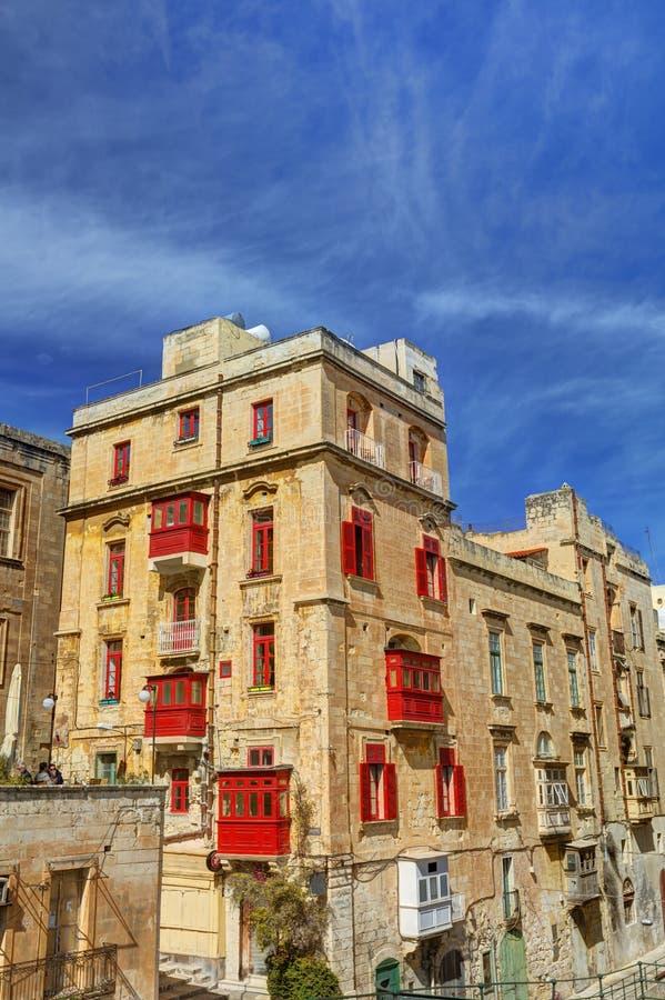 HDR fotografia stary historyczny budynek przeciw niebieskiemu niebu przy Valletta i z czerwonymi balkonami i okno, Malta obrazy stock