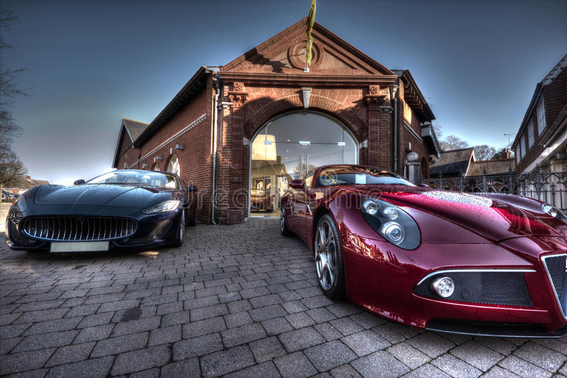 2 Sports cars parked outside a building royalty free stock photography