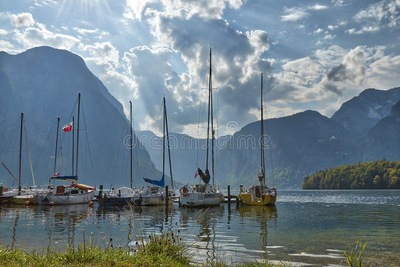 HDR landscape view of mountains with dramatic cloudy sky with anchoring yachts on the lake near Hallstatt village in Austria. HDR landscape view of mountains royalty free stock photo