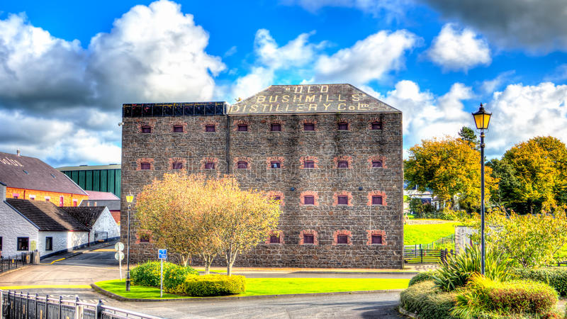HDR Old Bushmills Whisky Distillery in Ireland. Hight Definition Range photo of the old bushmills whisky distillery. Sunny bright cloudscape and multi colored royalty free stock image