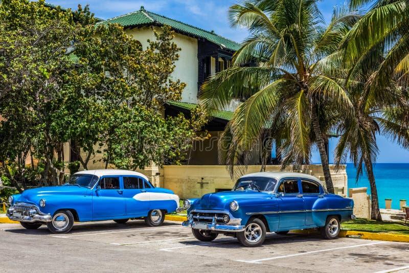 HDR - Os carros clássicos azuis americanos com telhado branco estacionaram na praia sob as palmas em Varadero Cuba - Serie Cuba foto de stock royalty free