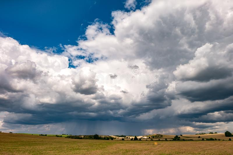 Hdr panorama on asphalt road among fields in evening with awesome black clouds before storm.  royalty free stock image