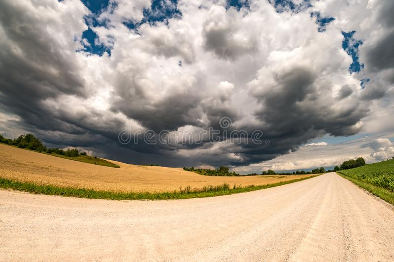 Hdr panorama on asphalt road among fields in evening with awesome black clouds before storm.  stock photography