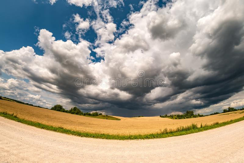 Hdr panorama on gravel road among fields in evening with awesome black clouds before storm.  royalty free stock image