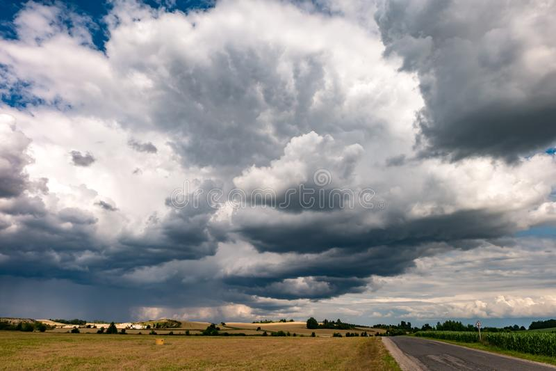 Hdr panorama on gravel road among fields in evening with awesome black clouds before storm.  royalty free stock images