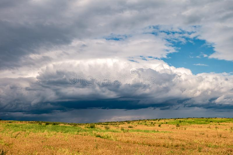 Hdr panorama on gravel road among fields in evening with awesome black clouds before storm.  stock image