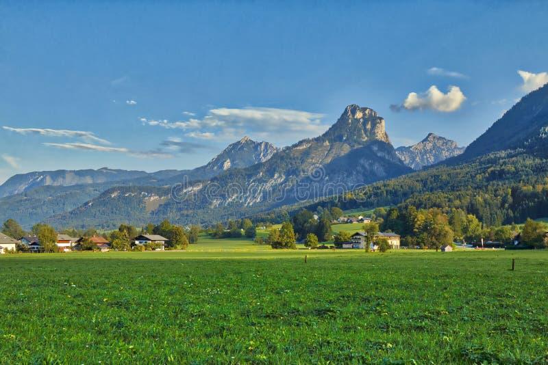 HDR piękny krajobraz z luksusowymi zielonej trawy gruntowymi i Alpejskimi górami blisko Wolfgangsee jeziora w Austria obraz stock