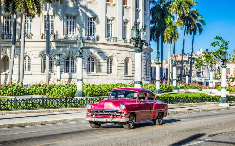 HDR - Street life view with american brown red Chevrolet vintage car drive before the Capitolio on the main street in Havana City royalty free stock photography