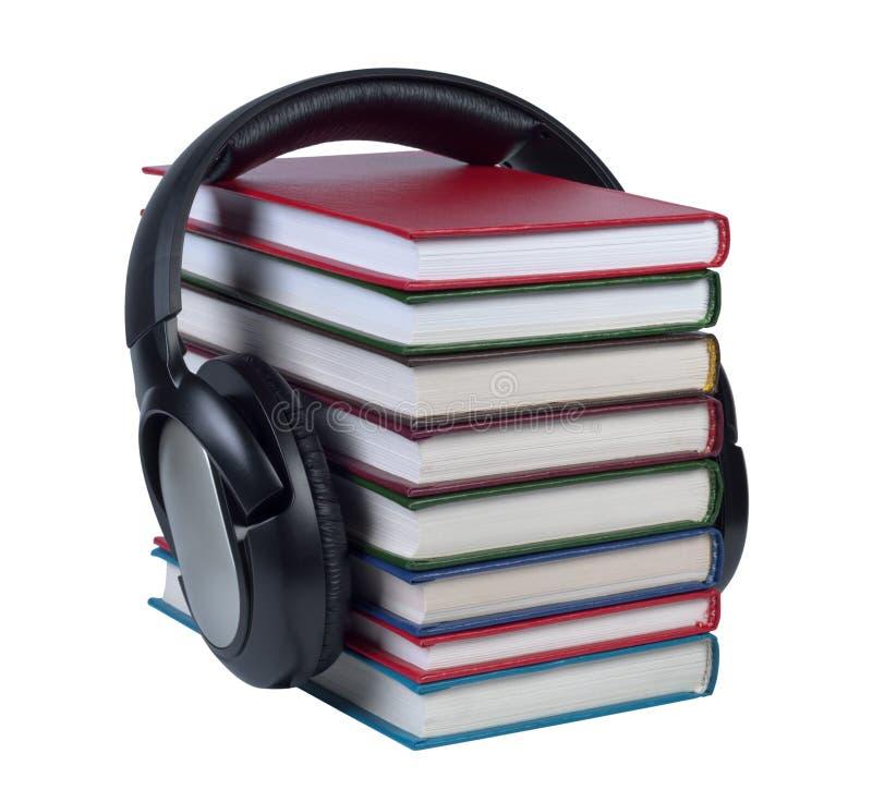 Hełmofony będący ubranym na stercie książki z kolor pokrywami. fotografia stock