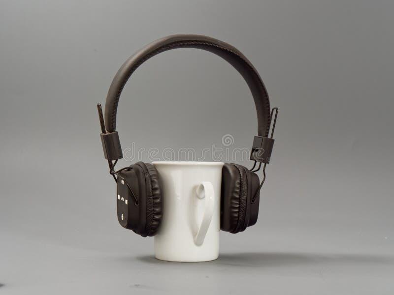 Hełmofony filiżanka i mysz stylizowany miłośnik muzyki na szarym tle obrazy stock
